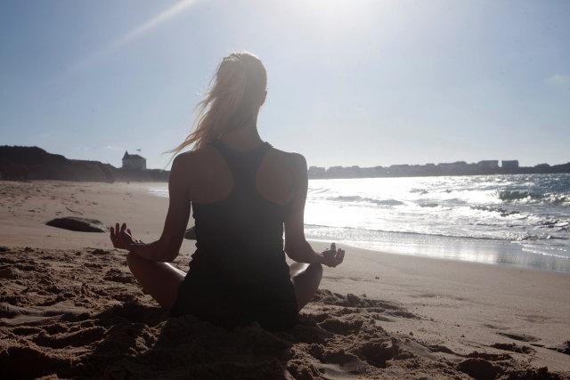 浜辺でヨガをする女性