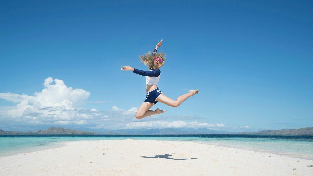 砂浜でジャンプする女性