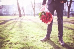 バラの花束を持つ男性